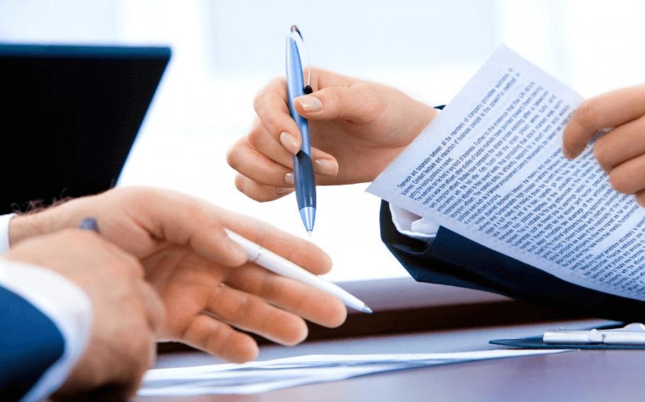 На фото изображен процесс проверки документов у нотариуса.