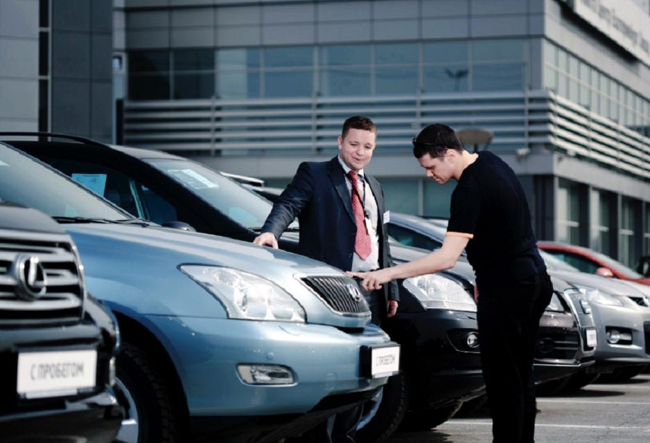 На фото изображен процесс осмотра и покупки автомобиля.