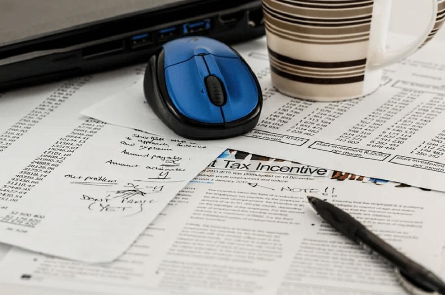 На фото изображены акты, договора и бланки по купле-продаже недвижимости.
