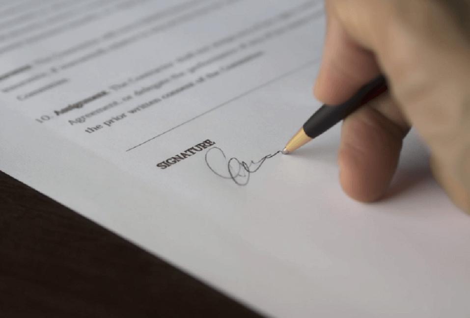 На фото изображен процесс подписания договора купли-продажи.