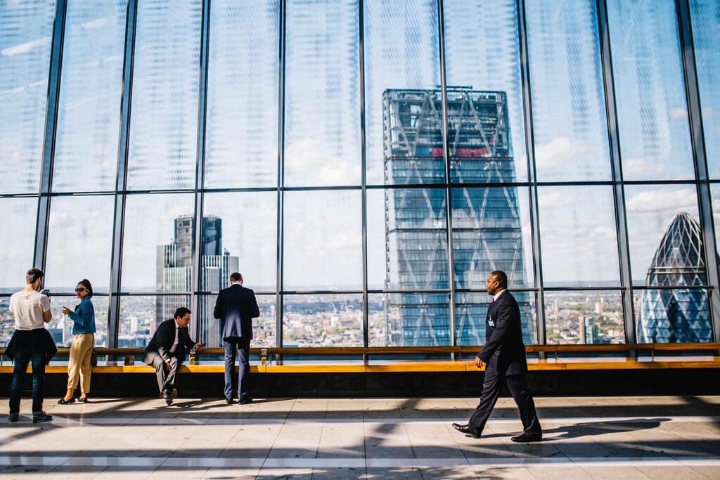 На фото изображено высокое здание, возле которого проходят люди.