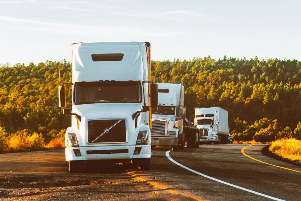 На фото грузовики едут по дороге.