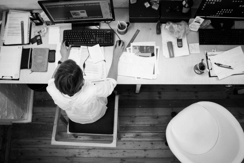 На фото офисный работник за компьютером.