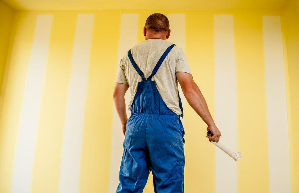 На фото мужчина красит стену.