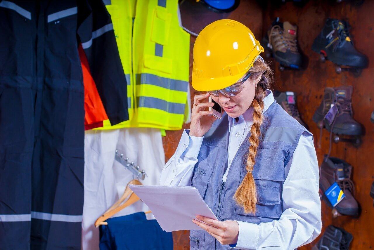 На фото девушка в каске читает договор.