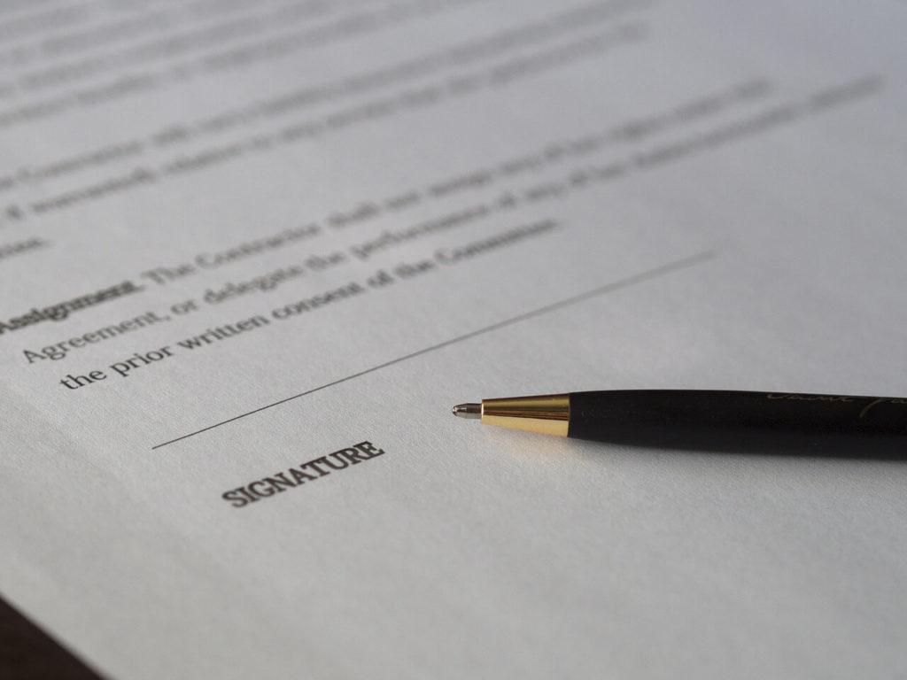 На фото ручка лежит на договоре.
