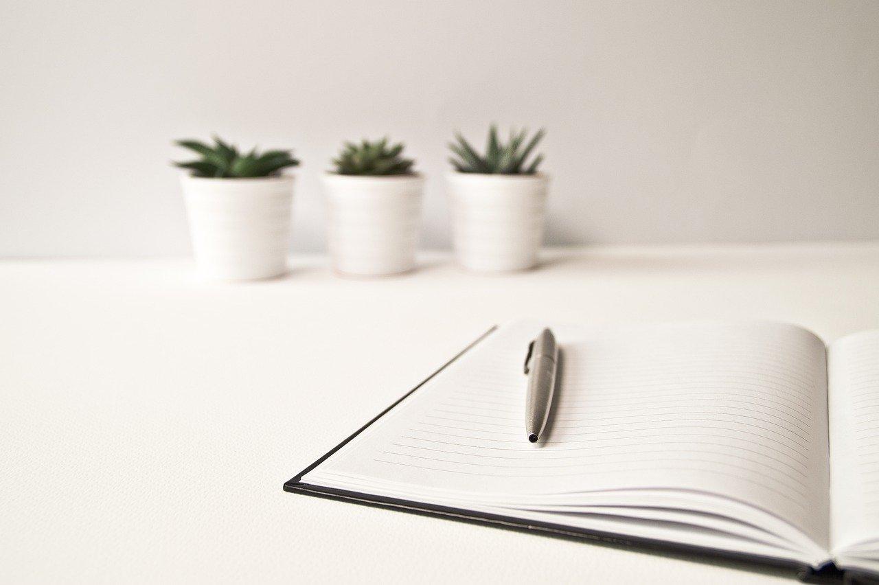 На фото ручка и блокнот лежат на столе.