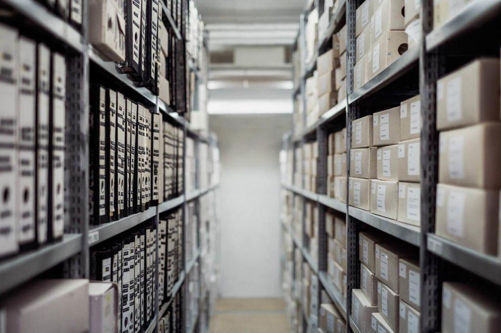 На фото изображены коробки на полках в нежилом помещении.