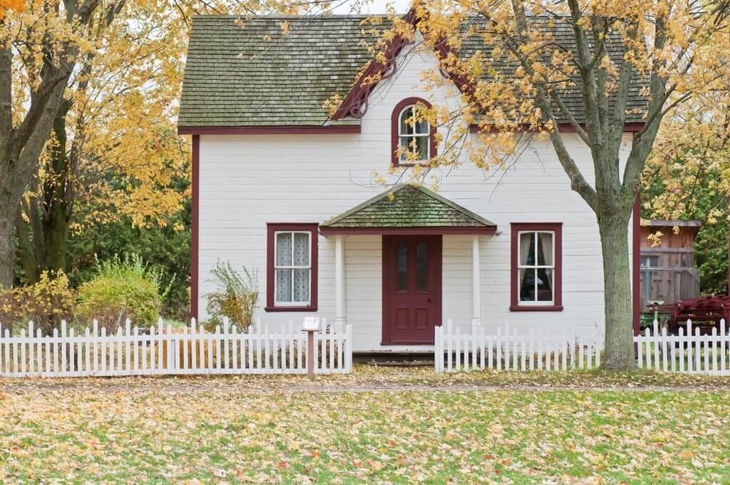 На фото изображен небольшой дом с невысоким забором.