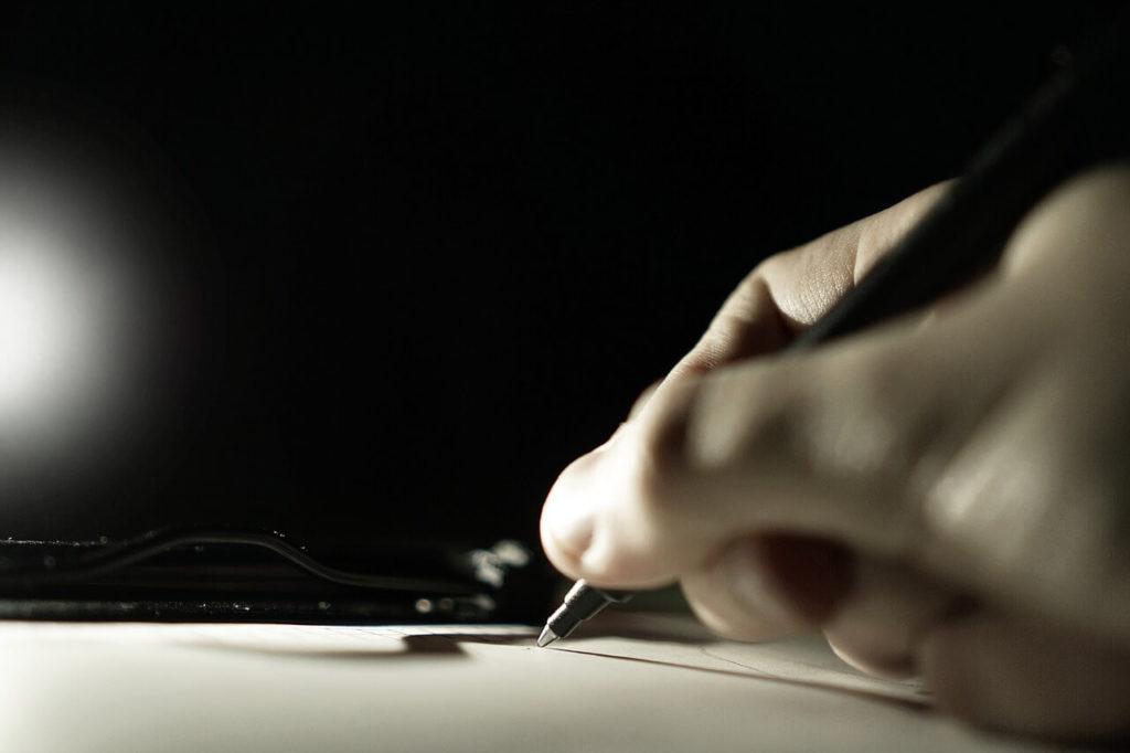 На фото человек пишет ручкой на листе бумаги.