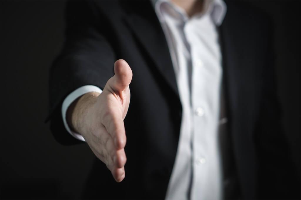 На фото человек в костюме хочет пожать руку.