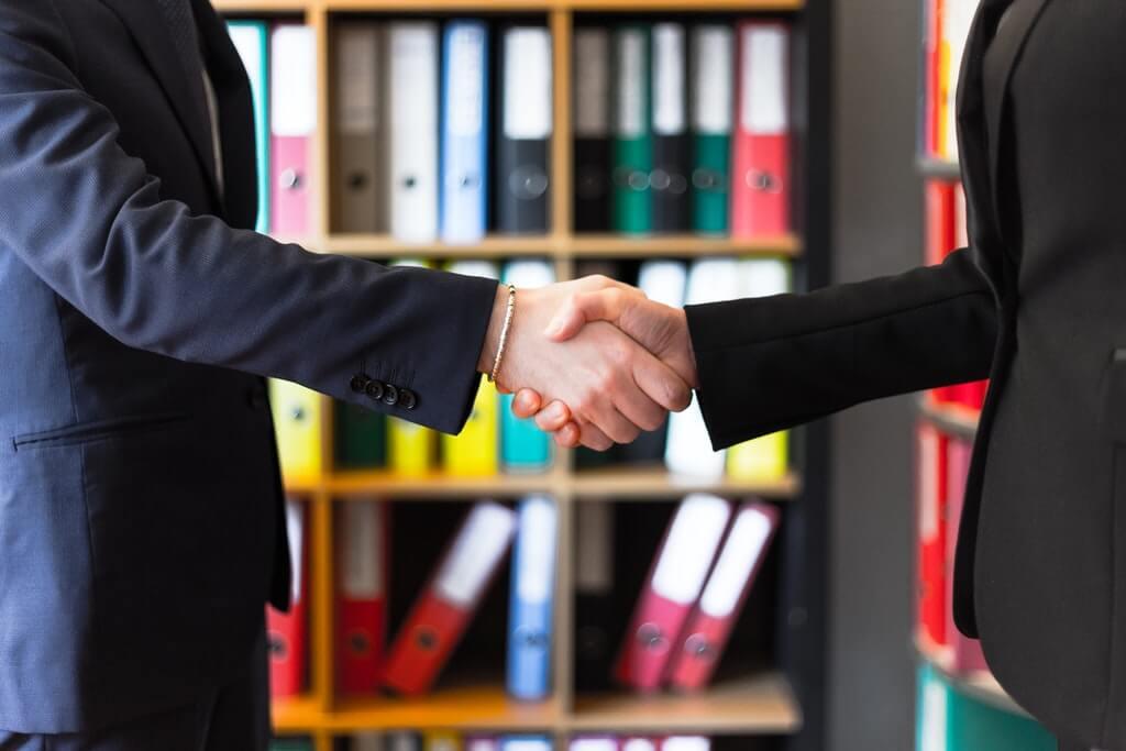 На фото люди жмут друг другу руки.