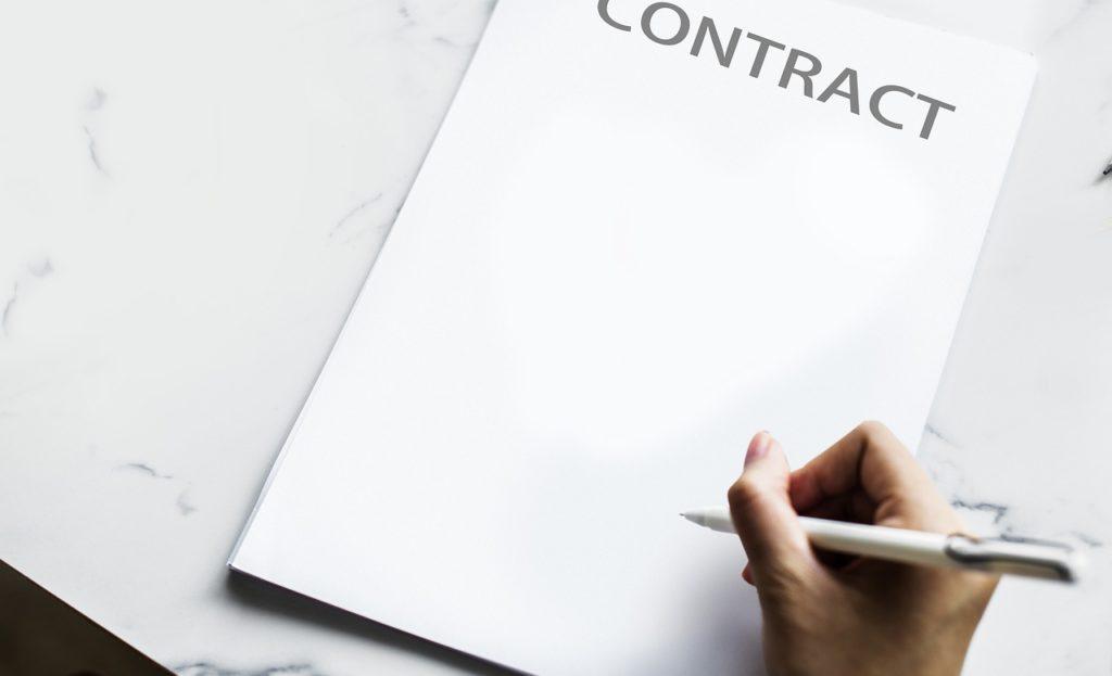 На фото человек подписывает контракт.