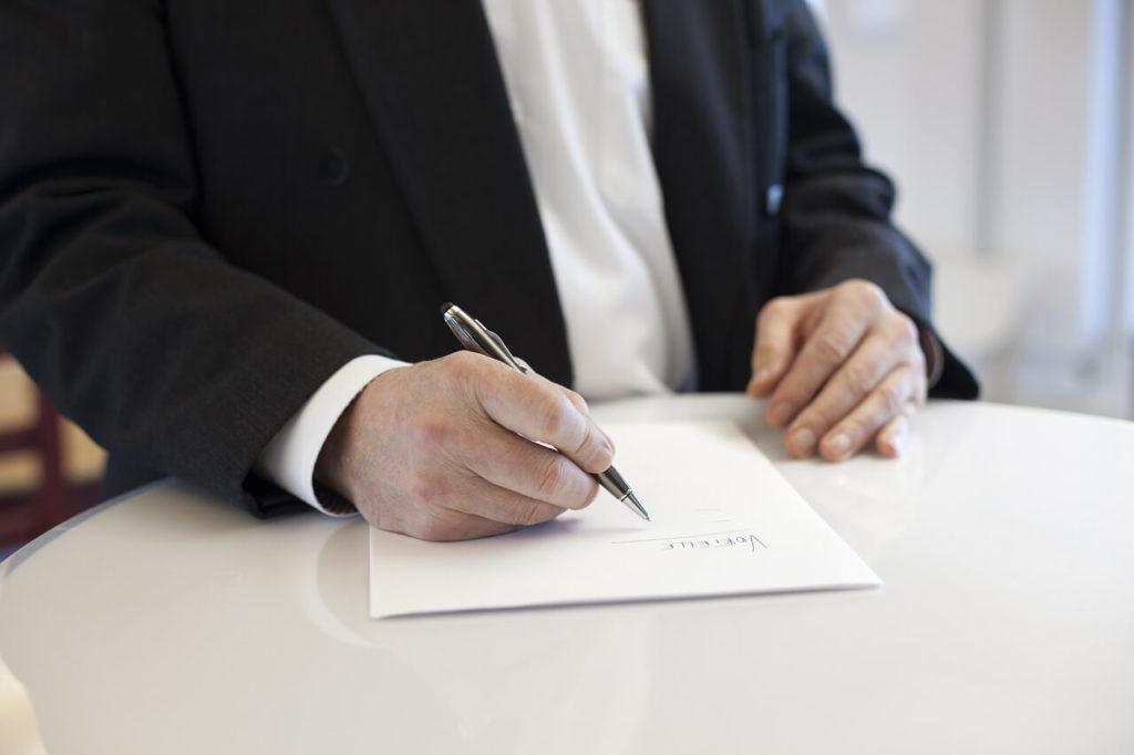 На фото мужчина в пиджаке подписывает договор.