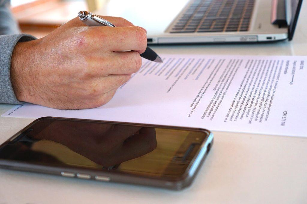 На фото мужчина читает договор с ручкой в руке.