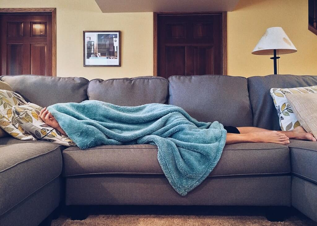 На фото мужчина спит на диване в комнате.