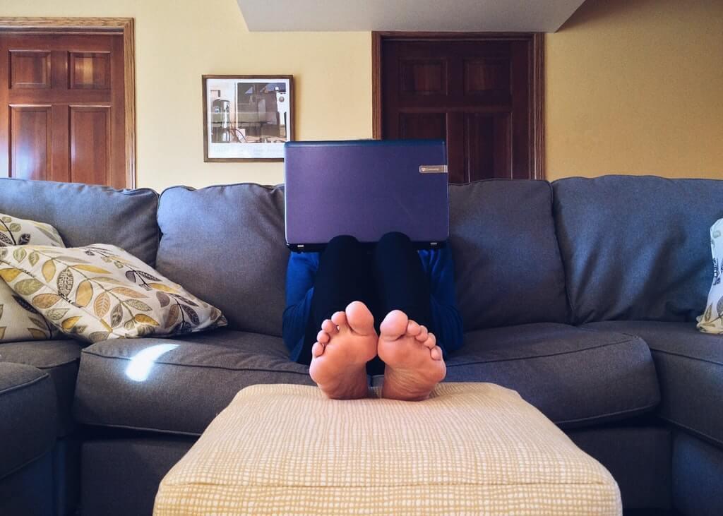 На фото мужчина с ноутбуком работает на диване.