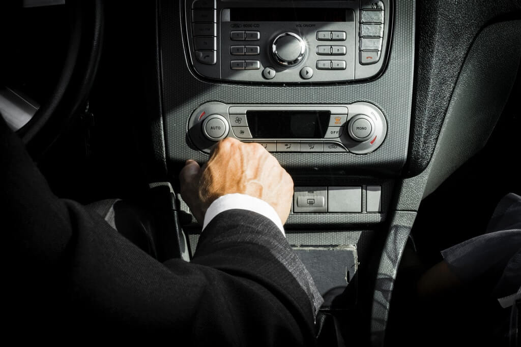На фото водитель за рулем автомобиля.