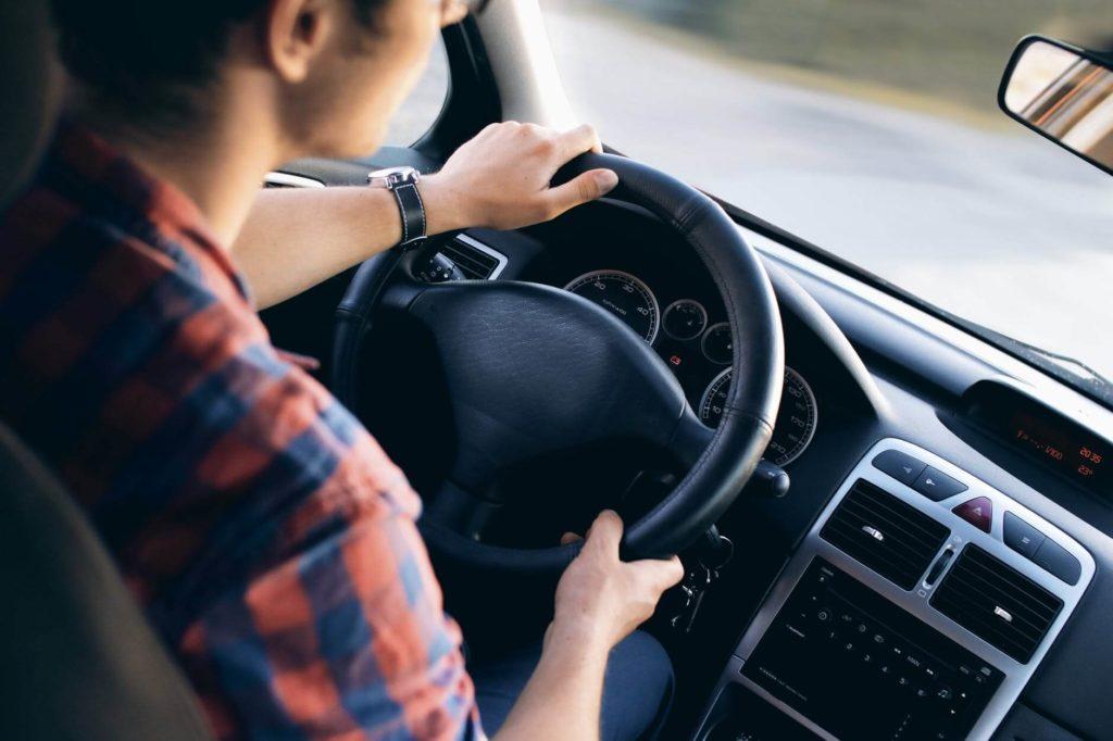 На фото парень за рулем автомобиля.