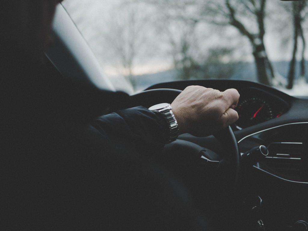На фото водитель держит руку на руле авто.