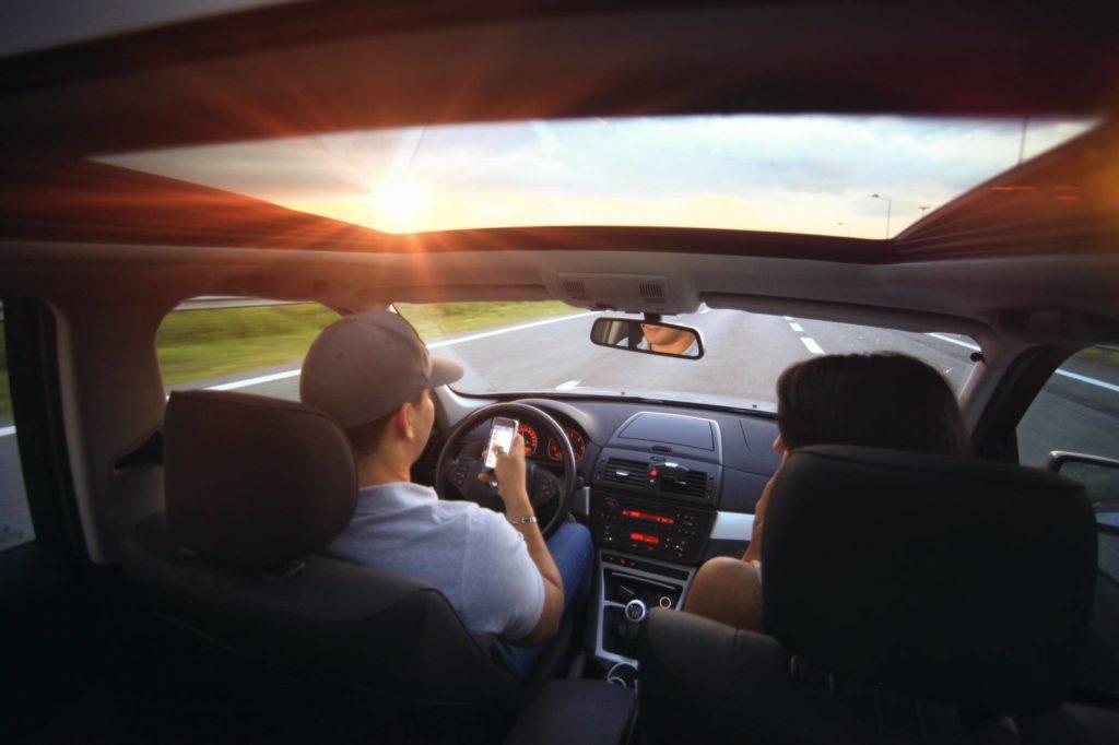 На фото пара едет на машине.