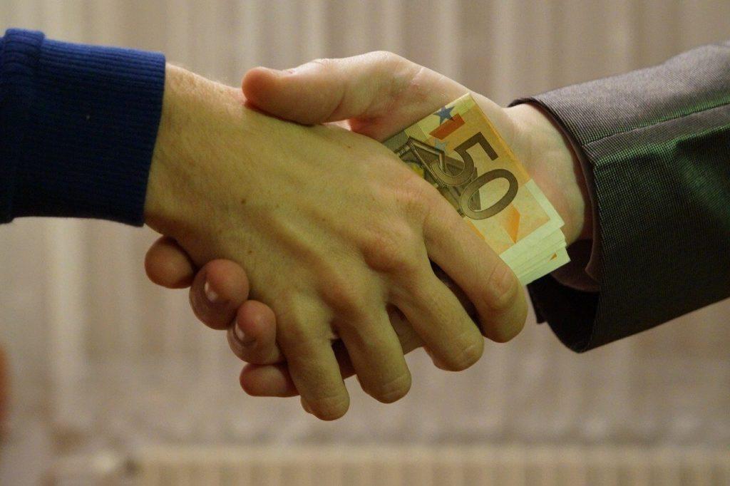 На фото один человек передает другому деньги во время рукопожатия.