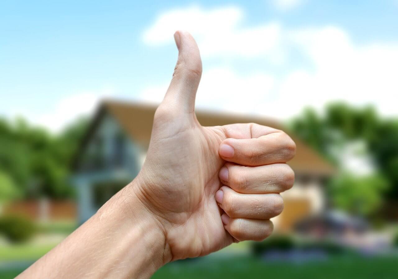 На фото изображена рука с пальцем вверх на фоне дома.