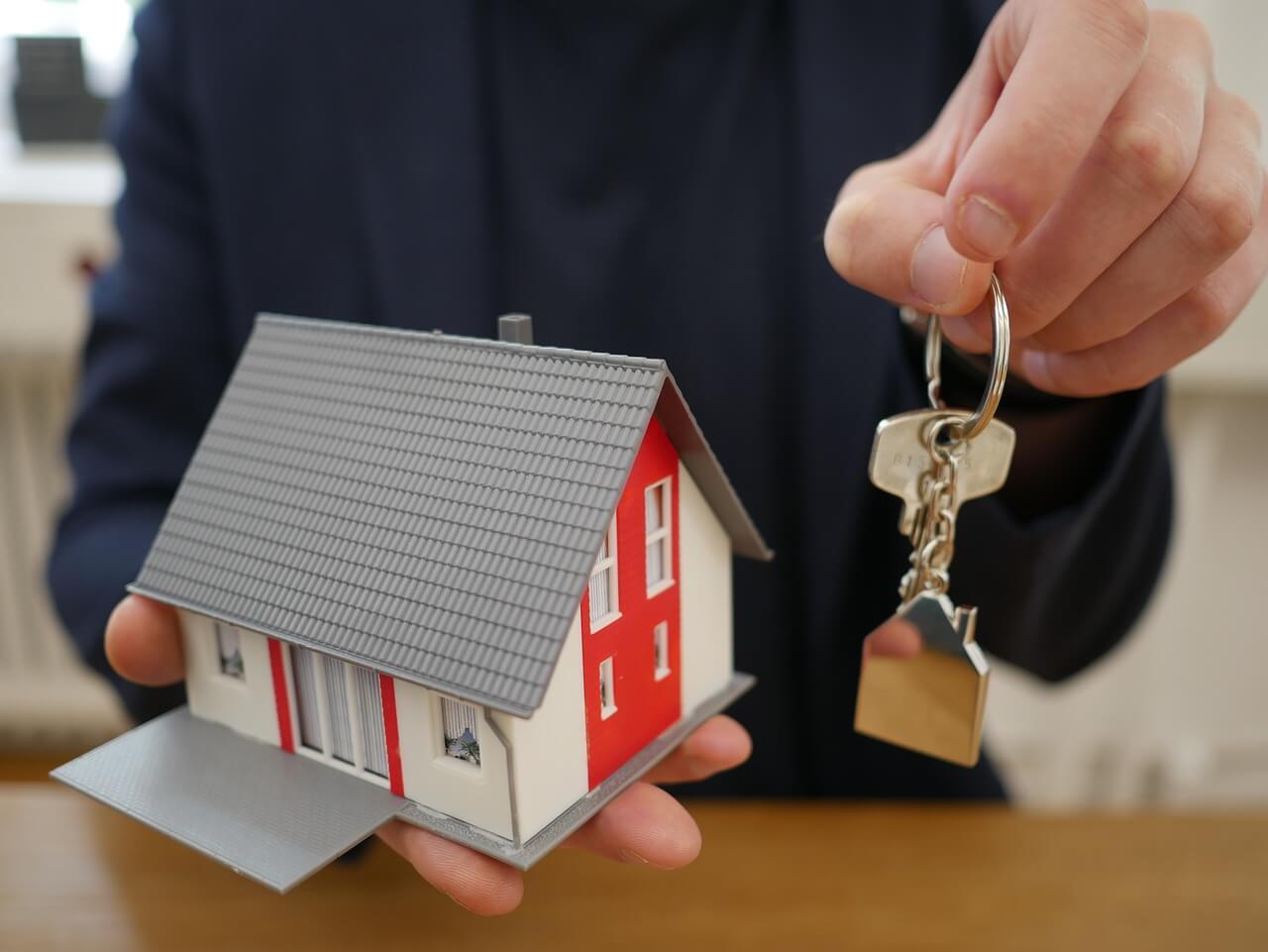 На фото изображен мужчина с ключами и макетом дома в руках.