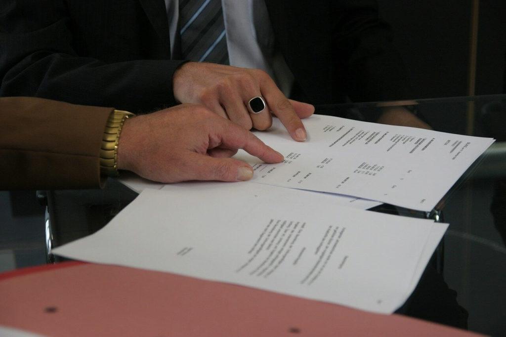На фото мужчины подписывают договор.