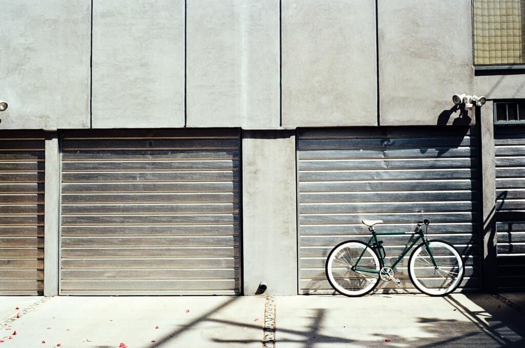 На фото изображен велосипед рядом с гаражом.