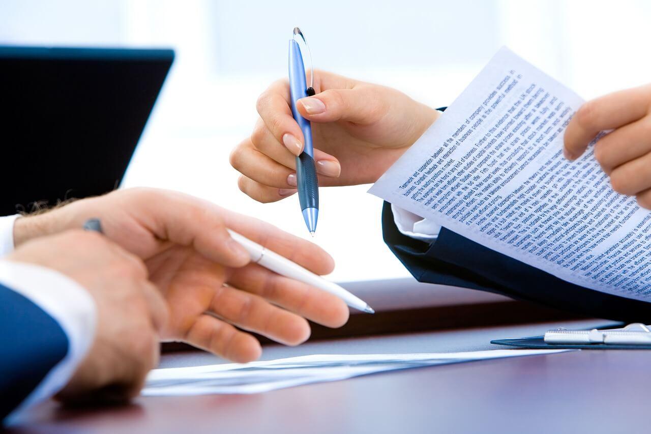 На фото два человека подписывают договор.