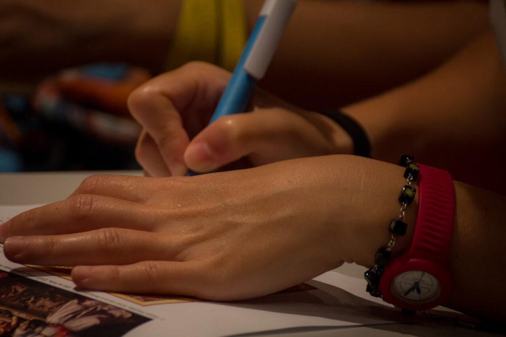 На фото девушка подписывает документ.
