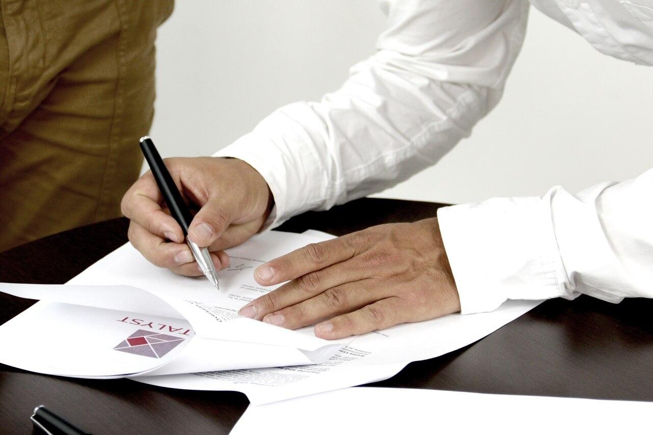 На фото мужчина подписывает документ.