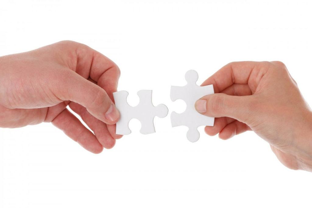 На фото изображены руки, которые держат пазлы.
