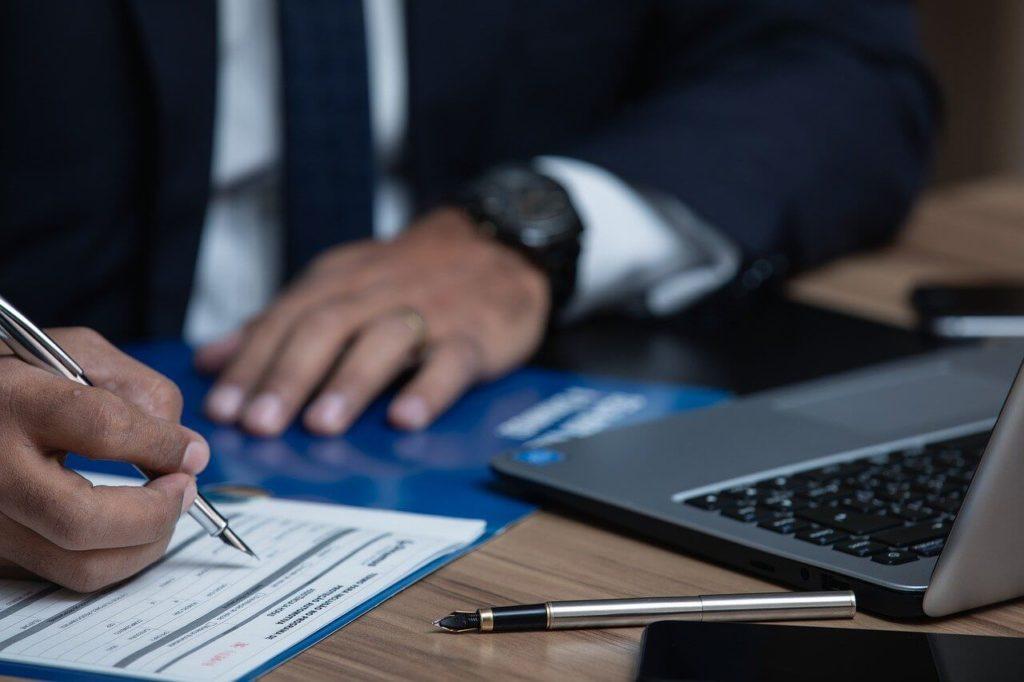 На фото мужчина в кабинете составляет договор.