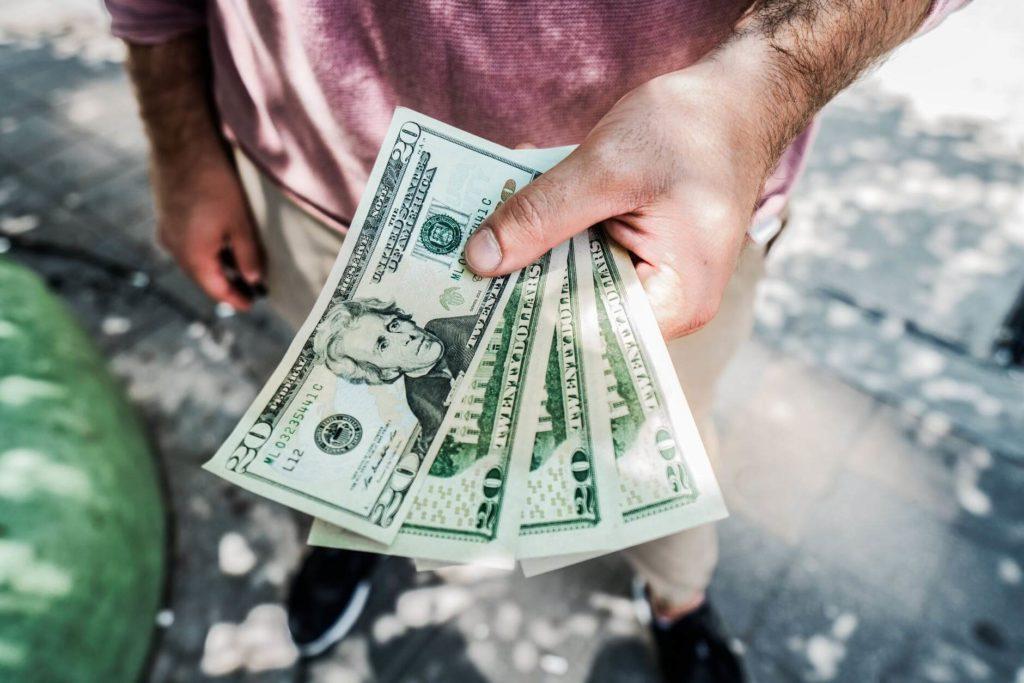На фото парень держит деньги в руке.