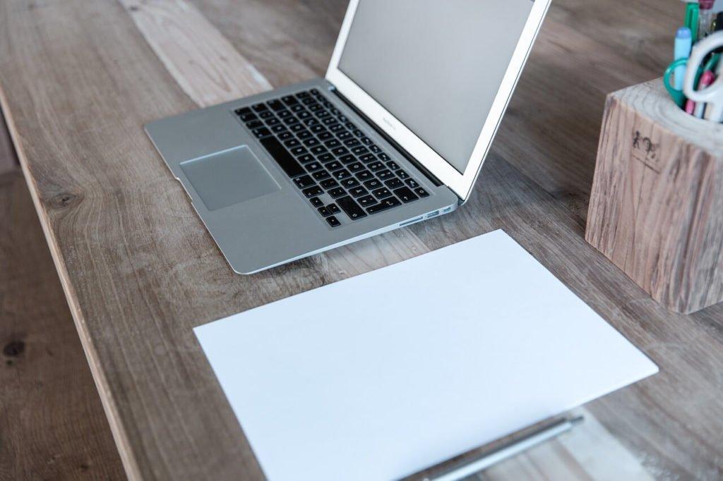 На фото ноутбук и бумага с ручкой на столе.