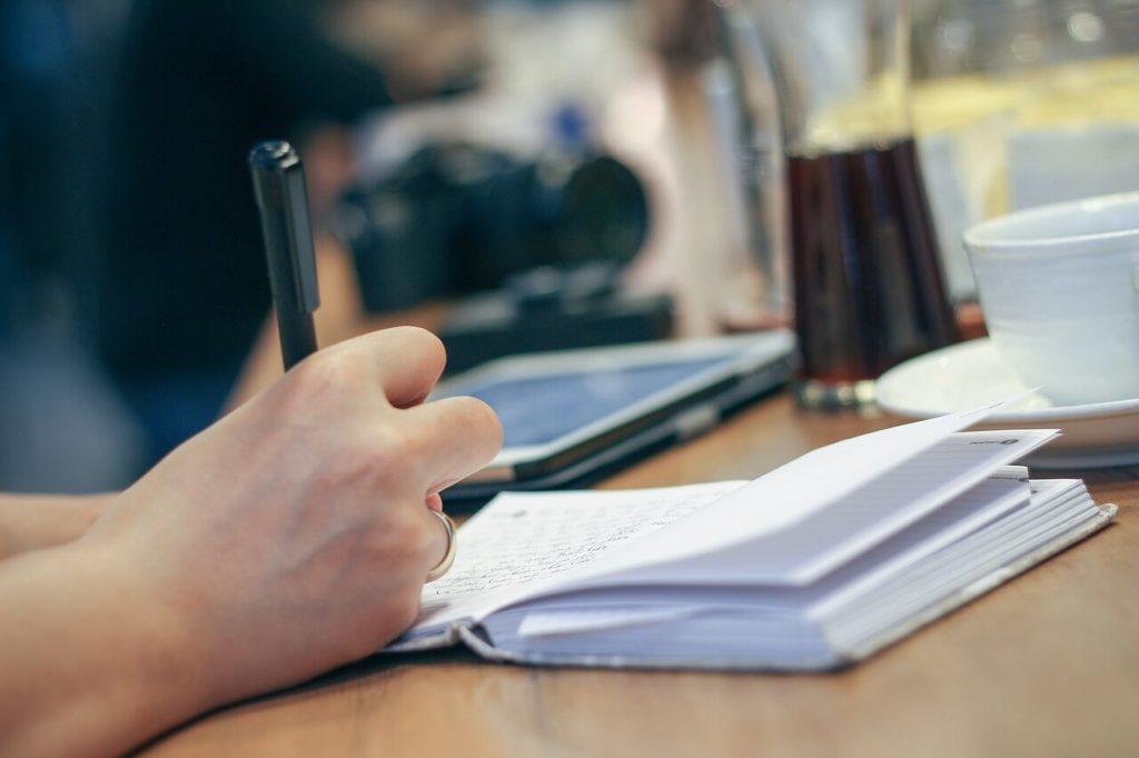 На фото человек что-то записывает в блокнот.