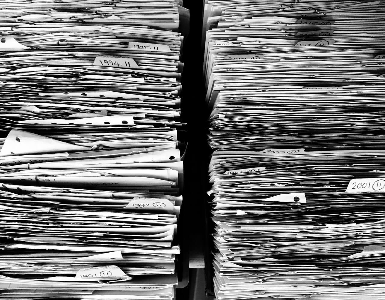 На фото изображены две стопки документов.