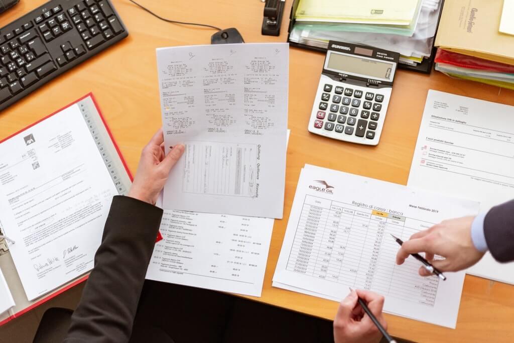 На фото мужчина на рабочем месте изучает документ.