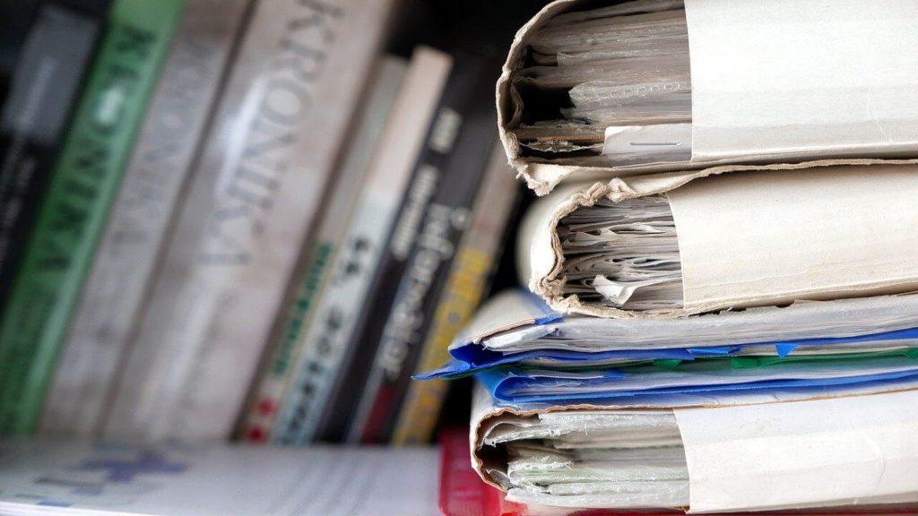 На фото изображены папки с документами, которые лежат на столе.