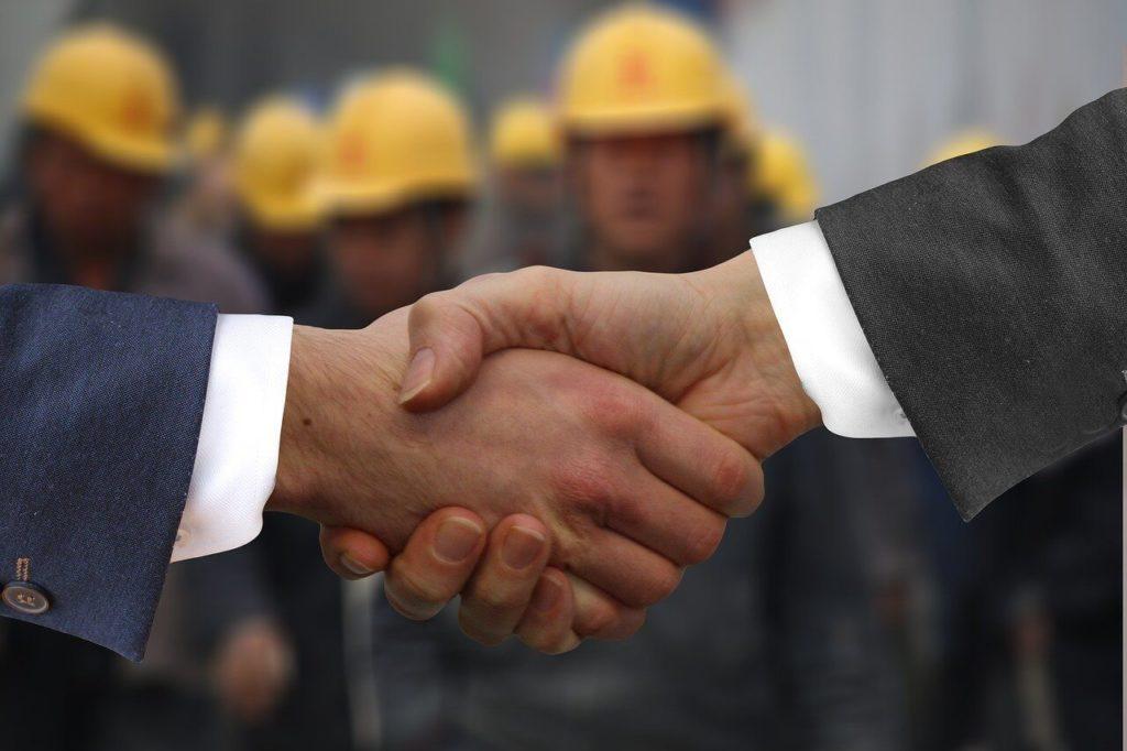 На фото изображено рукопожатие на фоне работников.