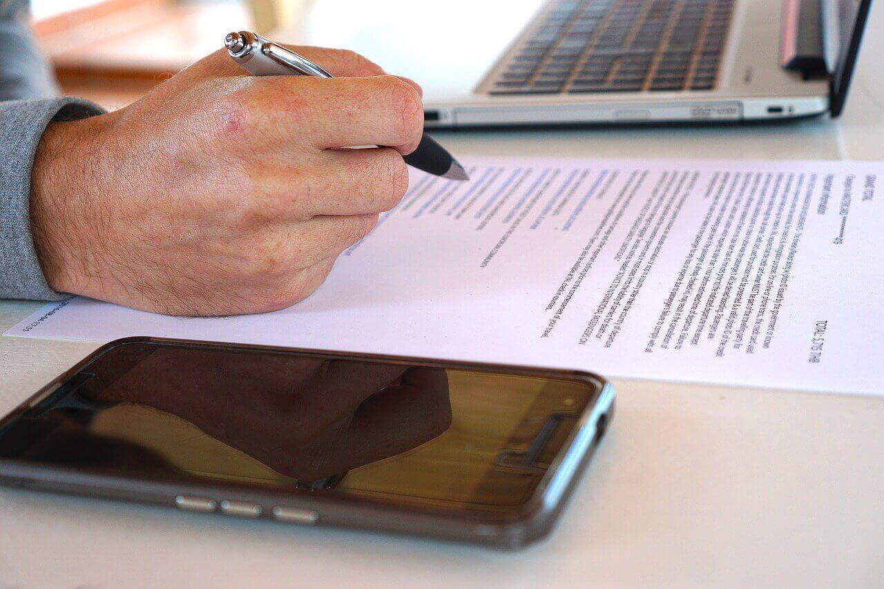 На фото мужчина читает договор.