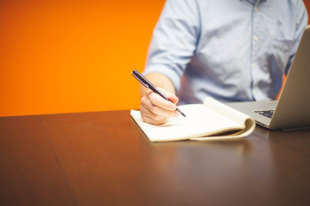 На фото мужчина работает за ноутбуком с ручкой в руке.