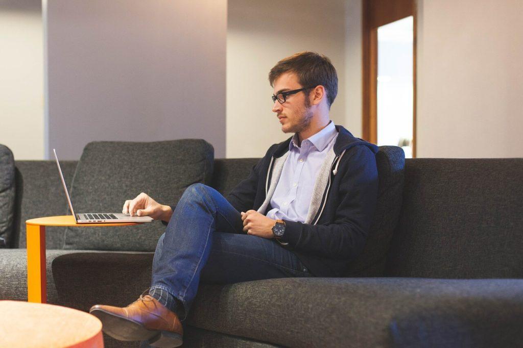 На фото молодой парень работает за ноутбуком.