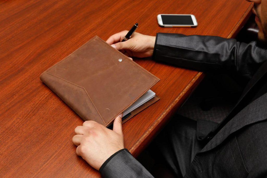 На фото изображен мужчина с папкой на за столом в офисе.