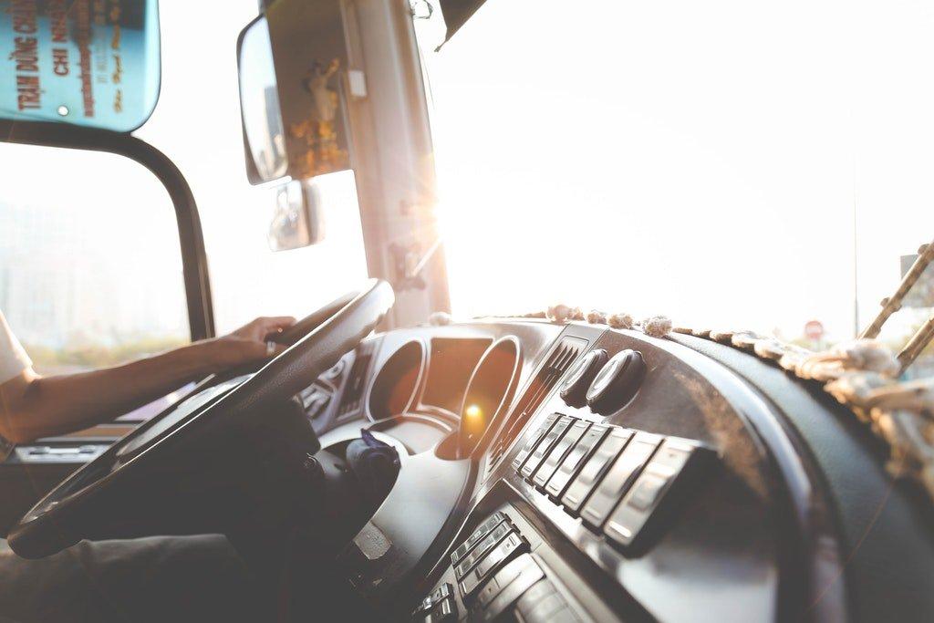 На фото водитель за рулем грузового авто.