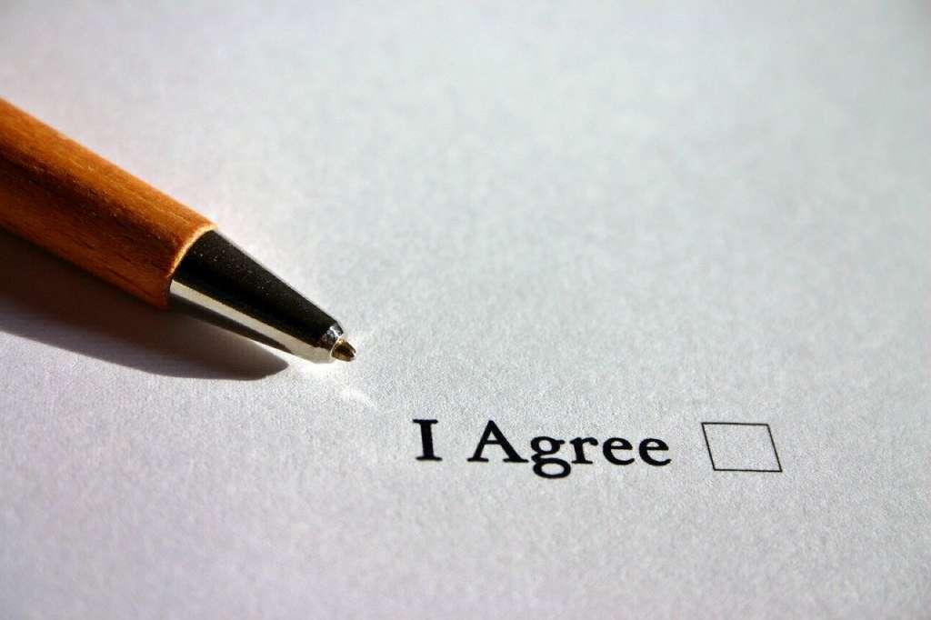 "На фото бумага и ручка возле слов ""я согласен""."