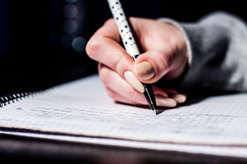 На фото девушка пишет ручкой на бумаге.