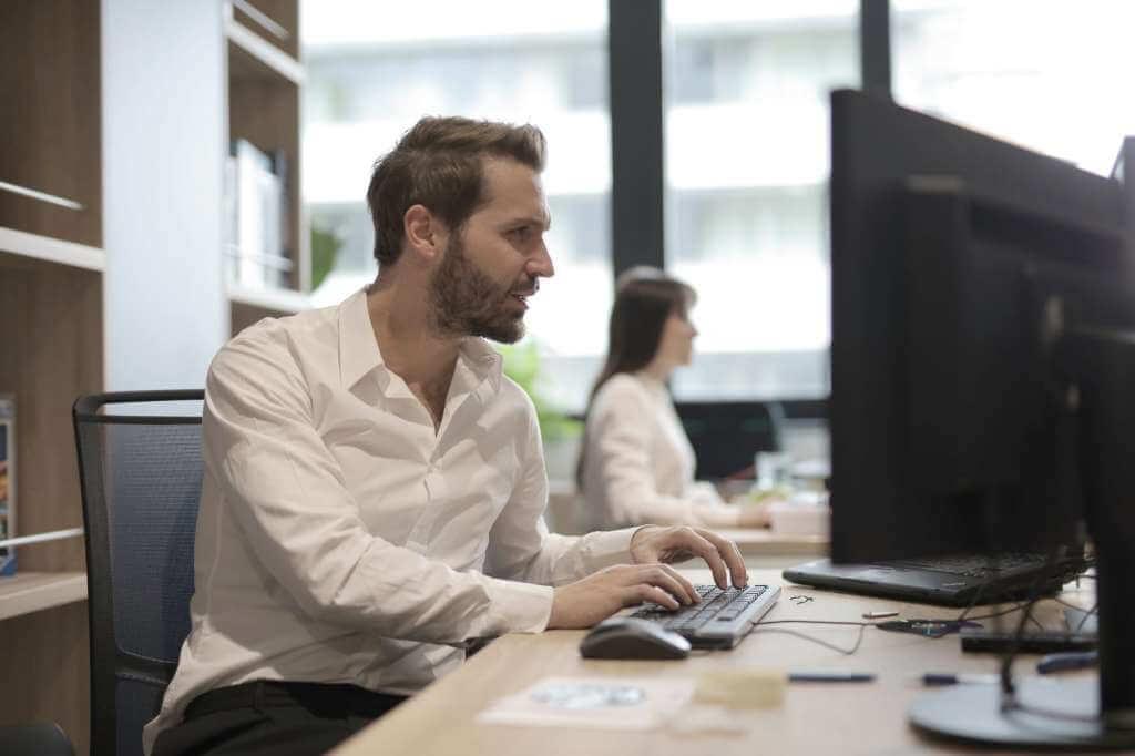 На фото мужчина работает в офисе.